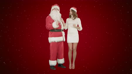 záradék : Santa Claus with excited pinup dancing woman on red background with snow Stock mozgókép