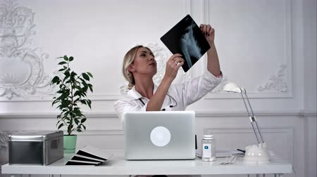 internar : Young female doctor looking for x-ray photo and making notes. Stock Footage