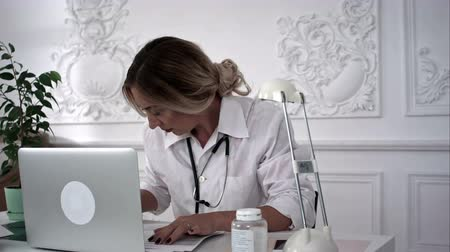 pediatria : Female doctor sitting at worktable and writing prescription on special form. Wideo