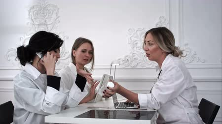 standing at table : Female doctors working with documents in medical office. Stock Footage