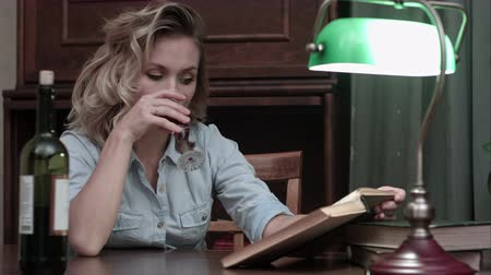 livro : Bored woman drinking a glass of wine sitting at a table and reading a book