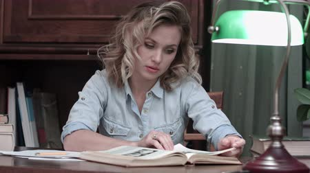 literatura : Young woman thoughtfully studying the book on her desk