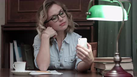 nerd : Young woman in glasses making selfies on the phone at her workplace Vídeos