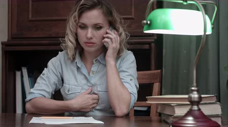 devastated : Tired young woman sitting at her desk receiveing very bad news on the phone Stock Footage