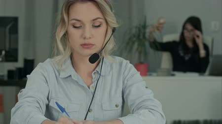 телефон доверия : Smiling female consultant with headset making notes while her coworker taking selfies
