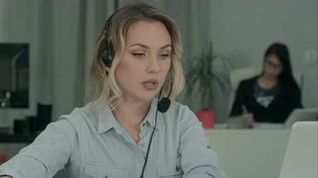 segregatory : Call center employee making notes while talking with customer Wideo