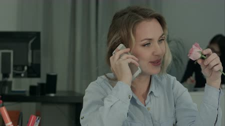 приемник : Happy female office worker talking on the phone and holding rose