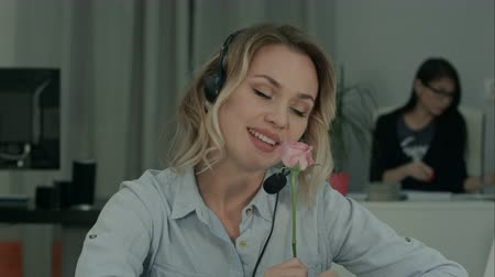 telefonkagyló : Pretty female office worker holding rose and talking to her secret admirer Stock mozgókép