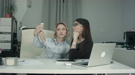 briefing : Two female colleagues taking selfie with phone in the office