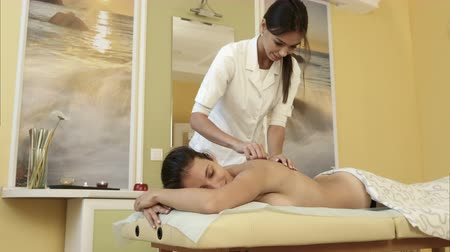 mumlar : Smiling masseuse doing massage on young woman body in a spa salon Stok Video