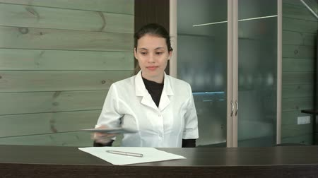 előcsarnok : Smiling spa receptionist putting her tablet aside to greet the client