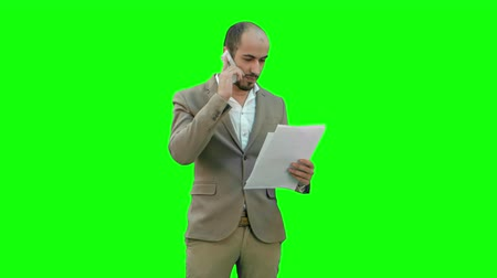 holding document : Young man in suit talking on the phone and holding papers on a Green Screen, Chroma Key.
