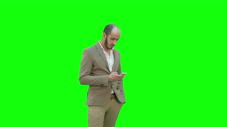 elküldés : Young man in suit walking and sending text message on mobile phone on a Green Screen, Chroma Key. Stock mozgókép