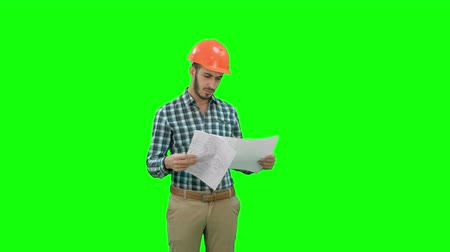 supervising : Engineer in hardhat looking at construction plan on a Green Screen, Chroma Key.