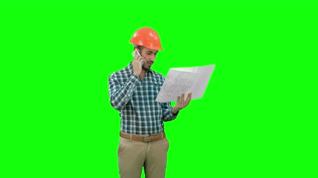 bossy : Site manager talking on the phone holding blueprints on a Green Screen, Chroma Key. Stock Footage