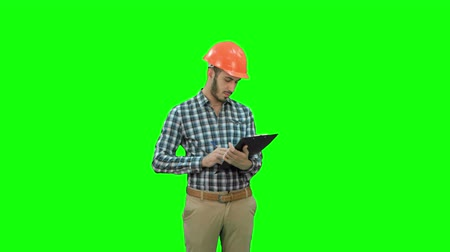 supervising : Young engineer in helmet inspecting construction site on a Green Screen, Chroma Key.