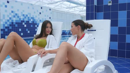 girl in robe : Happy female friends dressed in bathrobes and bikini relaxing at spa next to a swimming pool Stock Footage