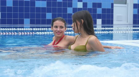 джакузи : Two happy female freinds enjoying jacuzzi in the swimming pool