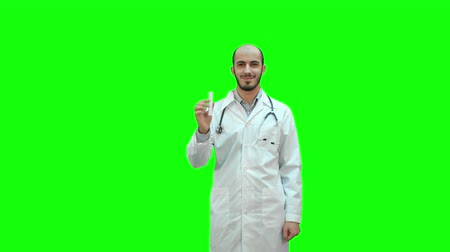 болеутоляющее : Young doctor presenting brand new medicine on a Green Screen, Chroma Key.