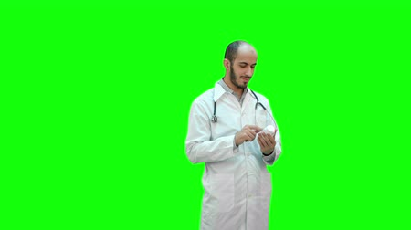 gyógyszerész : Male doctor attentively reading medicine label of a bottle of pills on a Green Screen, Chroma Key.