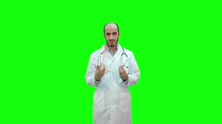 болеутоляющее : Doctor explaining difference between the pills on a Green Screen, Chroma Key. Стоковые видеозаписи