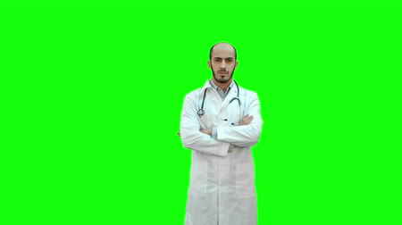 paramedics : Serious medical worker standing with his arms across his chest on a Green Screen, Chroma Key. Stock Footage