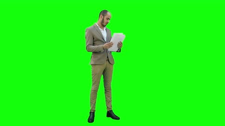 looking down : Young businessman attentively studying documents on a Green Screen, Chroma Key.