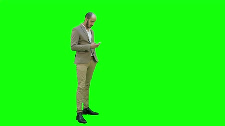 looking down : Business man walks in checking up his phone on a Green Screen, Chroma Key. Stock Footage