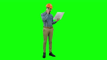 kravata : Site manager talking on mobile phone holding blueprints on a Green Screen, Chroma Key.