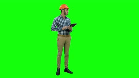 supervising : Engineer in helmet inspecting construction site on a Green Screen, Chroma Key.