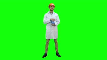 çöküş : Engineer in helmet and white coat starting building demolition on a Green Screen, Chroma Key.