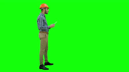 гражданский : Contractor engineer inspecting construction site holding digital tablet on a Green Screen, Chroma Key.