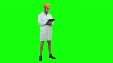 chroma key background : Civil engineer in white coat preparing report on a Green Screen, Chroma Key.