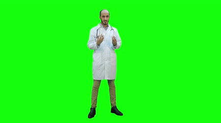 antykoncepcja : Doctor explaining difference between two bottles of pills on a Green Screen, Chroma Key.