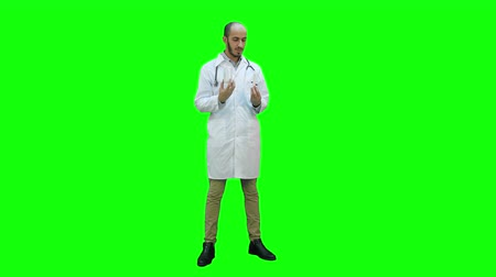 antykoncepcja : Male doctor describing two different pills on a Green Screen, Chroma Key.