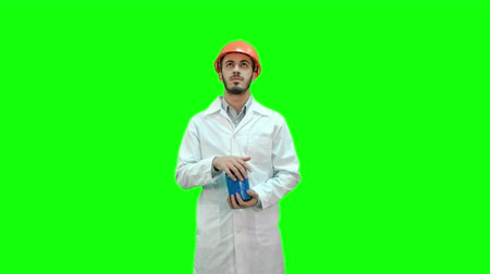 destruct : Engineer in helmet and white coat launching demolition on a Green Screen, Chroma Key.