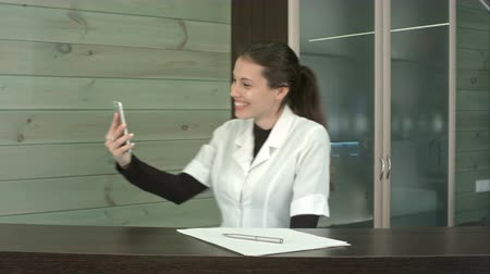 registration : Happy spa manager taking selfies with her phone at the reception desk