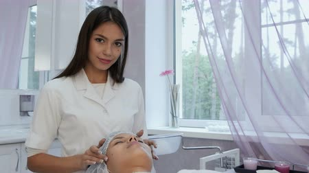 restful : Beautiful cosmetologist giving a young woman facial massage at beauty spa