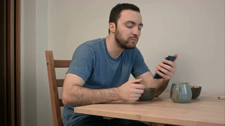 hot news : Young man using phone while eating breakfast Stock Footage