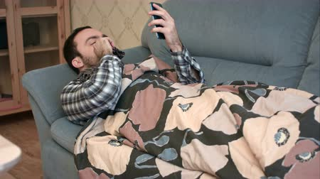grypa : Sick man in scarf lying on the sofa and using phone