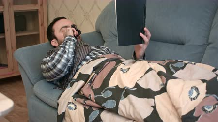 respiratory infection : Young man reading book while lying sick on the sofa