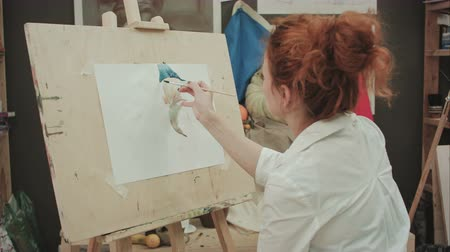 tintas : Young female artist painting still life in studio