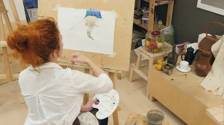 stationary : Ginger female artist using aquarelle to paint still life