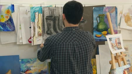 adultos : Young man hanging paintings on string in art class Stock Footage