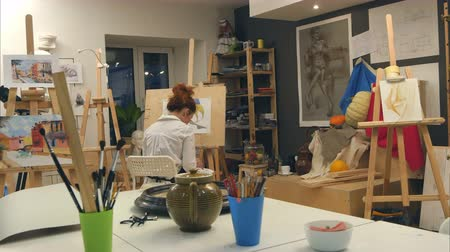 borracha : Ginger female artist painting still life in art studio Stock Footage