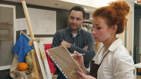 piada : Two positive art students laughing in the studio