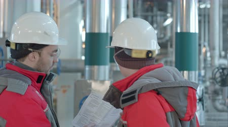 petroleum refinery : Two chemical factory workers having conversation in plant. Stock Footage