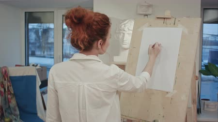 biust : Female art student drawing plaster cast on easel
