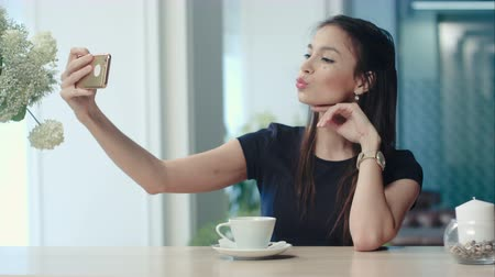 bolt : Smiling young woman taking selfies on her phone at the cafe