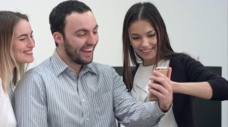 alliance : Three cheerful coworkers taking funny selfies on the phone Stock Footage
